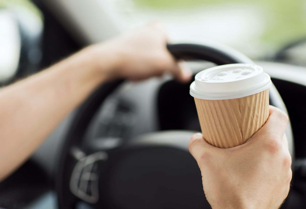 Person driving whilst holding coffee cup