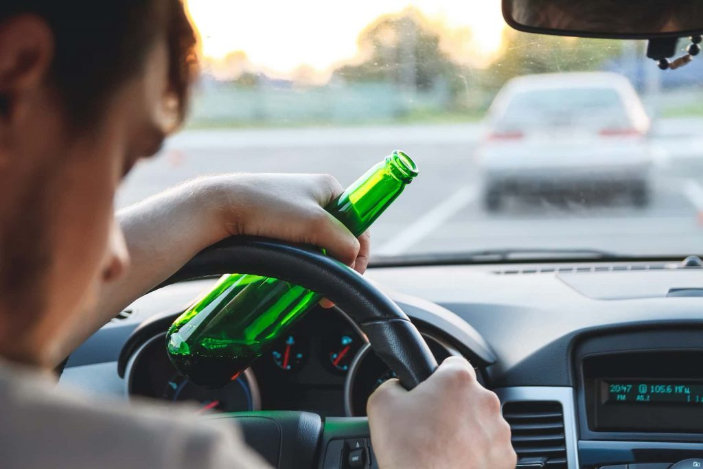 Image of a drunk Temecula driver drinking a beer whilst driving and who may be in trouble if stopped at one of the many new DUI checkpoints.