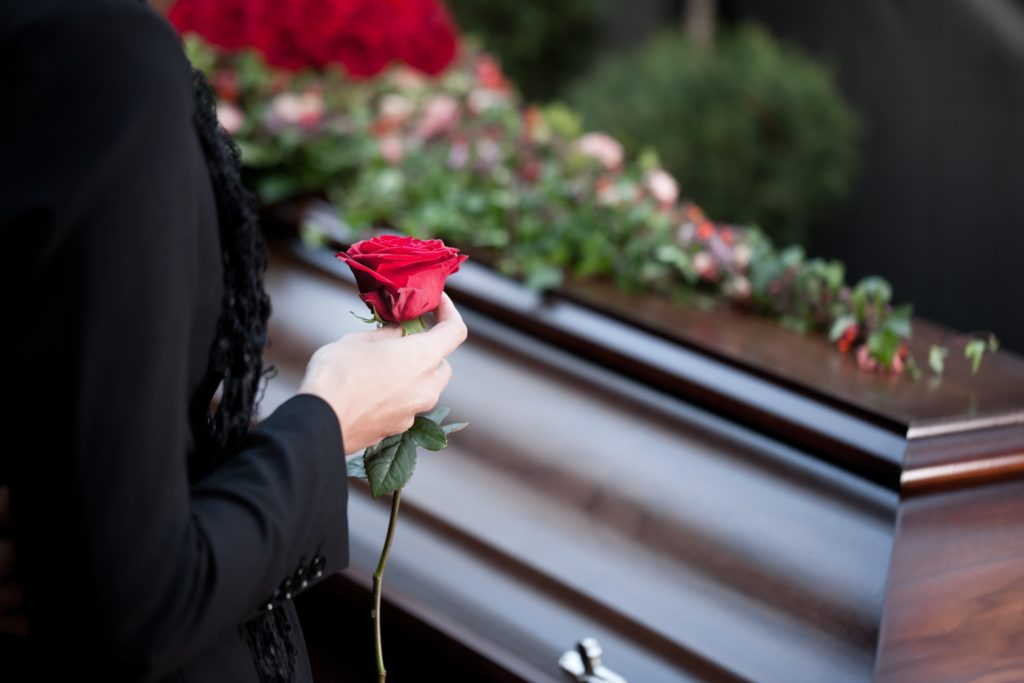 Image of a red rose on a coffin