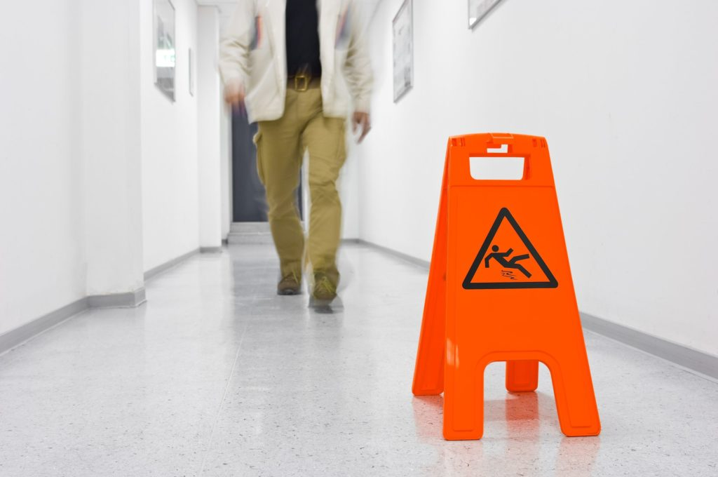 Caution sign indicating slippery floor with man walking up in background