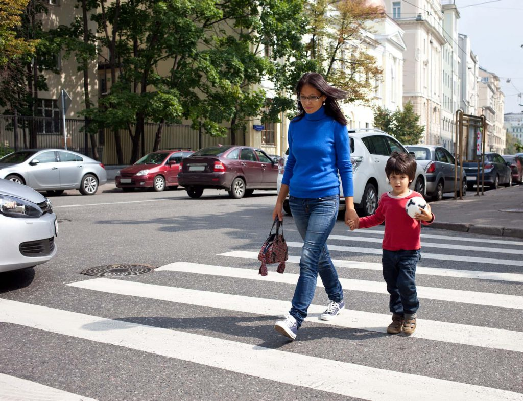 Image of a mother and her son walking across a pedestrian crossing.