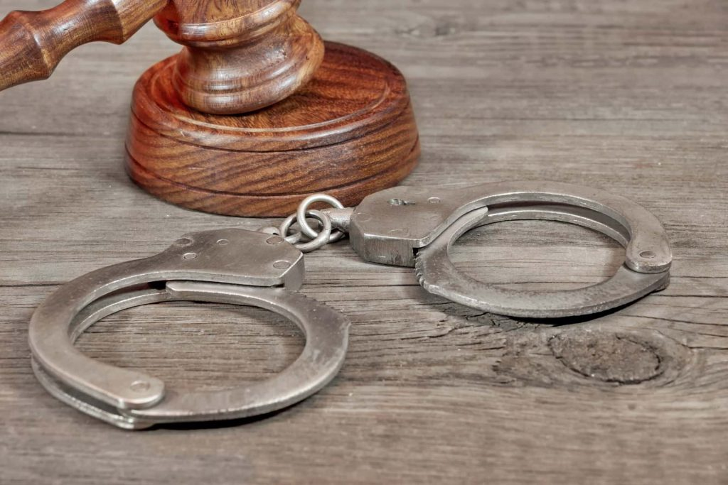 Pair of handcuffs on a desk next to a gavel
