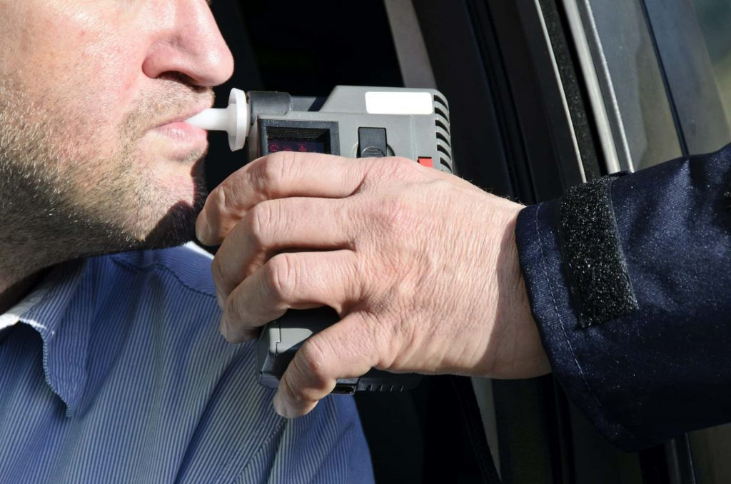 Image of a man giving a breathalyzer test after being stopped at a Murrieta DUI checkpoint that resulted in multiple arrests.