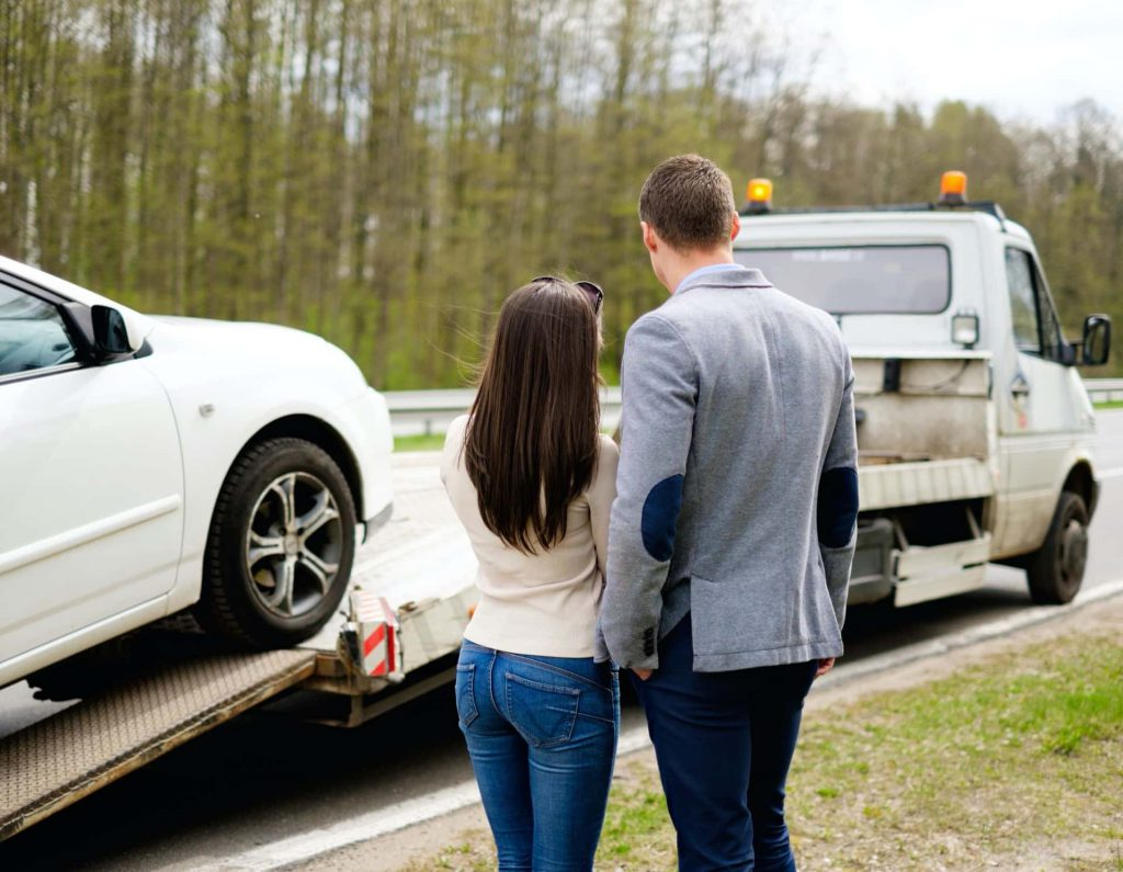 Couple watching their car be towed away after an auto accident