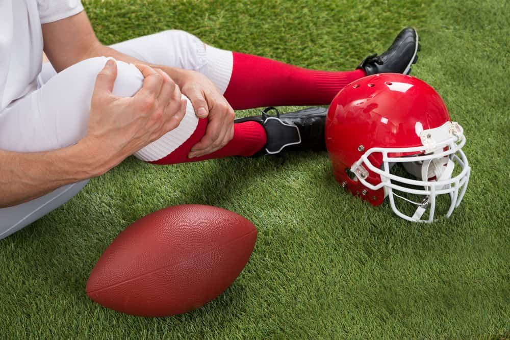 Image of a seated Temecula football player who has sustained a serious knee injury but is remaining positive and hopeful